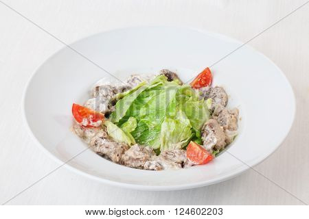 salad with meat in a creamy sauce, ase, lettuce, romaine, iceberg cherry tomatoes on top of the plate isolated white background series menu