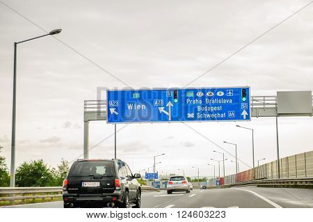 AUSTRIA - SEP 19 2013: European highway sign - direction and exit sign to Praha Bratislava and Budapest Wien. Useful file for your flyer about European road infrastructure and other with cars passing fast under the sign