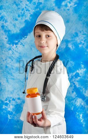 Boy in white doctor costume and stethoscope holding orange bottle with pills on blue background