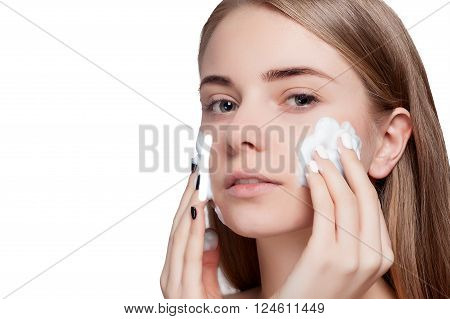 Beautiful woman cleaning her face with a foam treatment on a white light background. Beauty Portrait. Beautiful Spa Woman Smiling. Perfect Fresh Skin. Pure Beauty Model. Youth and Skin Care Concept