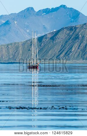 Red schooner motoring into bay past mountains