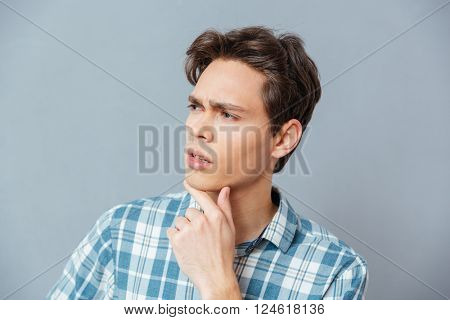 Pensive casual man looking away over gray background