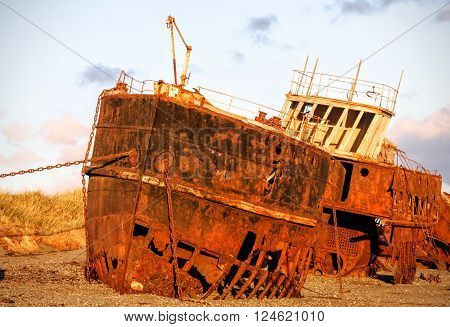 Rusted ship wrecked on beach at sunset with purple clouds.