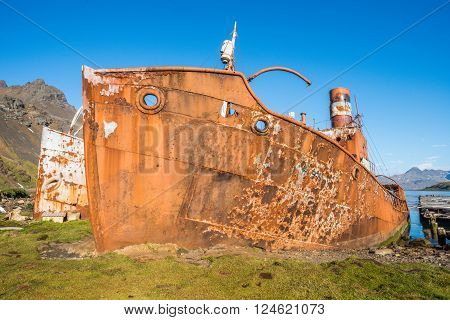 Two rusty old whalers beached beside dock