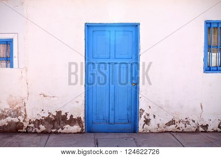 Bright blue door in white wall with chipped paint