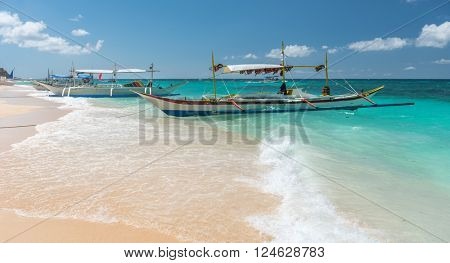 traditional filipino asian ferry taxi tour boats on puka beach in tropical boracay island at philippines