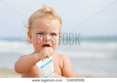 Adorable girl at beach applying sunblock cream portrait