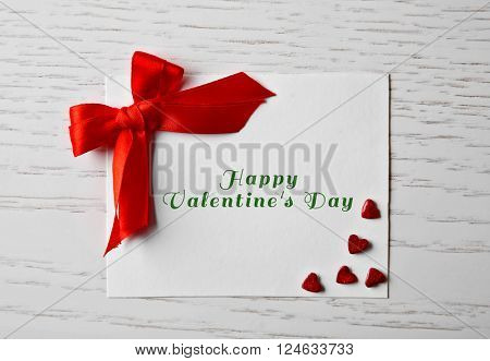 Blank present card with ribbon bow and small hearts on wooden background
