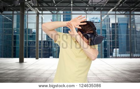 3d technology, virtual reality, entertainment and people concept - scared young man with virtual reality headset playing game over empty industrial room and city panorama background