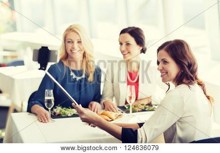 people, holidays, celebration and lifestyle concept - happy women with smartphone selfie stick taking picture at restaurant