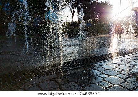 Modern and beutifull waterfall with sun in the back. Water drops dancing with people in the back