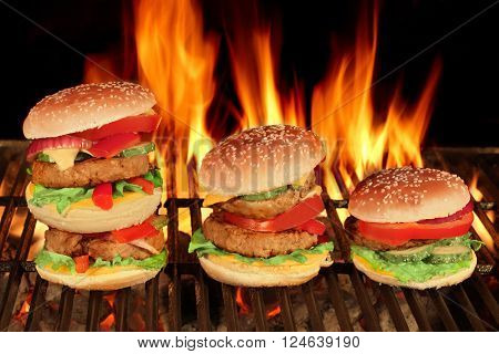 Three Different King Size Homemade Cheeseburgers In A Row On The Hot BBQ Grill With Flame Of Fire On The Black Background Close Up Front View
