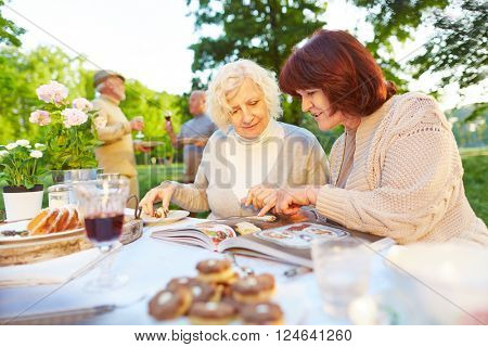 Two elderly women reading cookbook while eating cake in a garden