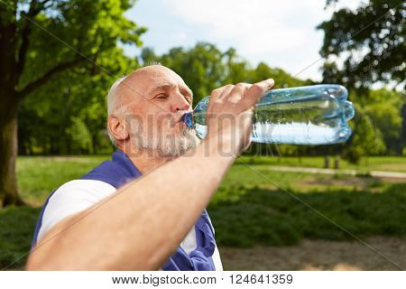 Thirsty senior man drinking a bottle of fresh water after doing sports
