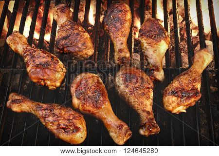 BBQ Grilled Chicken Legs On The Hot Flaming Grill Top View. Cookout Food Good Snack For Outdoor Party Or Picnic