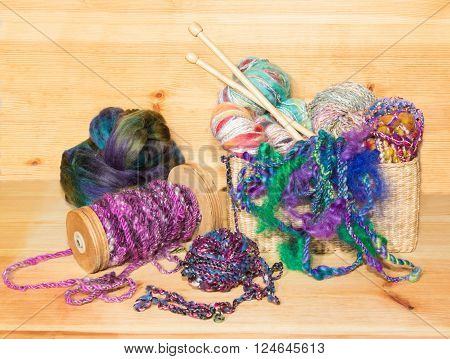 Various types of fancy art yarns in a basket with a spindle and a wool fleece ready to knit.