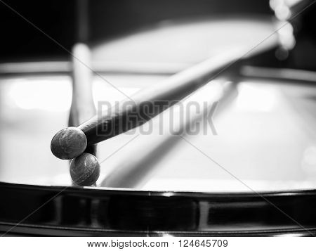 Music concept photo of the pair of wood drumsticks on drum in black and white style.