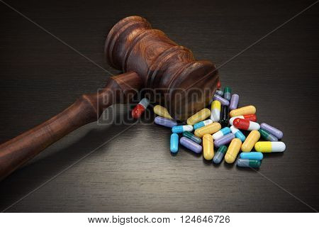 Judges Gavel And Medication On Black Wood Grunge Background