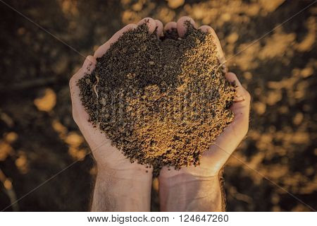 Male farmer holding pile of soil and examining its quality on fertile agricultural land agronomist preparing land for new crop raising season close up of hands.