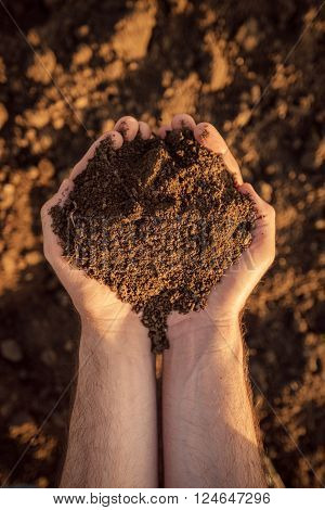 Arable land soil in hands of a responsible farmer male caucasian farmer holding pile of soil agronomist preparing land for new crop raising season close up of hands.