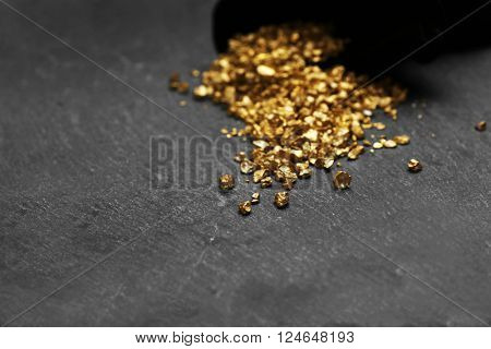 A pouch with scattered gold nugget grains, on cement background