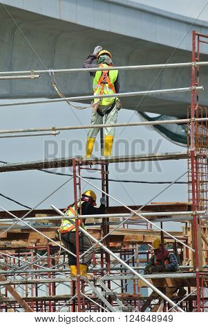 SELANGOR, MALAYSIA -FEBRUARY 23, 2016: Construction workers wearing safety harness and installing scaffolding at high level in the construction site in Selangor, Malaysia.