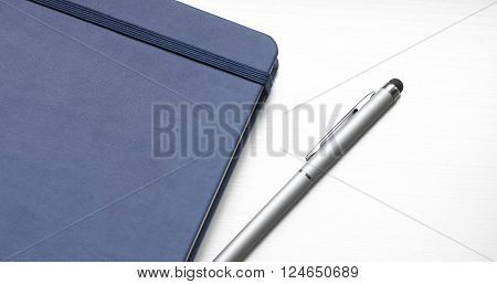 On the table lies a diary and a pen. The gray and blue pen diary on the table. Businessman Notepad and pen stylus. Diary of leather and metal handle with a stylus.