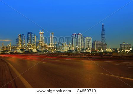beautiful city scape of road and land transportaiton against lighting of oil refinery industry plant use as energy and fuel power topic background