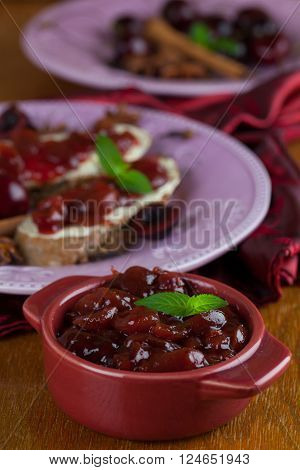 Homemade spicy cherry jam in a bowl and bread in the background