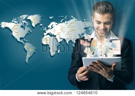 Financial concept. Make money on the Internet. Handsome businessman holding tablet on world map background