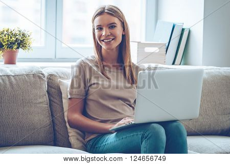 Surfing net with joy. Beautiful young woman using her laptop and looking at camera with smile while sitting on couch at home