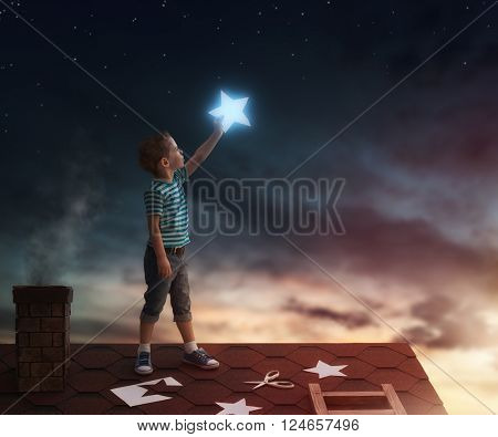 Fairy tale! The child hanging the stars in the sky. Boy on the roof cuts out stars.