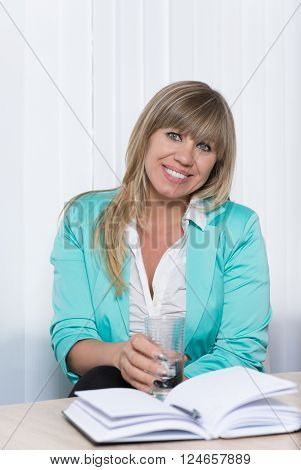 A smiling businesswoman is holding a glass of water while sitting at a table in the office. The woman is looking to the camera.