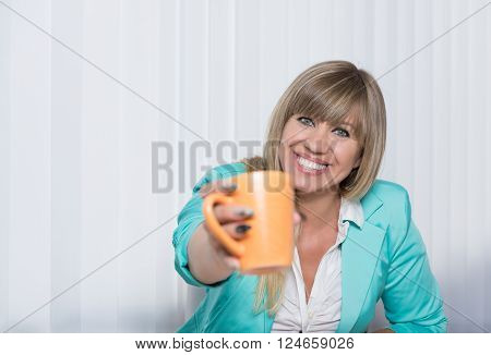 A smiling businesswoman is handing over a cup of coffee. The woman is looking to the camera.