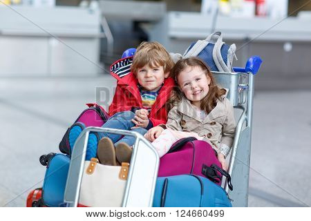 Two adorable little siblings, kid boy and girl sitting on suitcases on international airport. Brother and sister, happy family wating for flight and going on vacations.