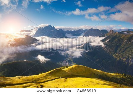 Great view of the foggy Val di Fassa valley. National Park Dolomites (Dolomiti), pass Sella. Location famous resort Canazei, Tyrol, Alp, Italy, Europe. Dramatic and picturesque scene. Beauty world.