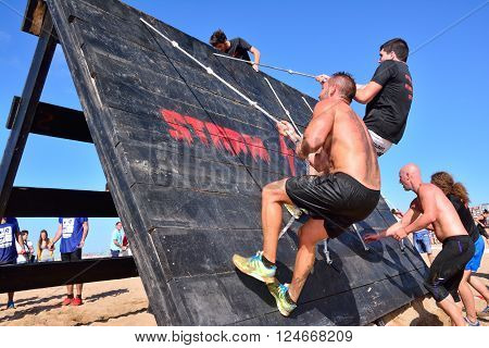 GIJON SPAIN - SEPTEMBER 19: Storm Race an extreme obstacle course in September 19 2015 in Gijon Spain. Participants in extreme obstacle course jumping a wooden wall.