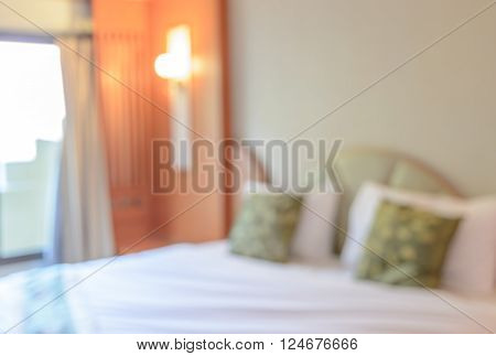 Blur image background of white bedroom with tidy bed and pillows