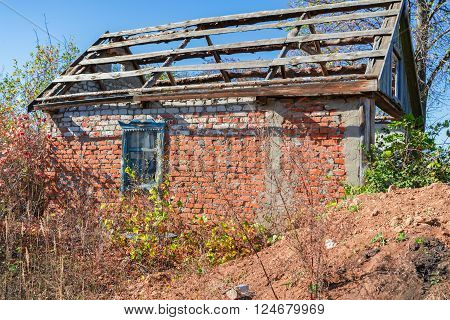 An old abandoned brick house with a broken window, closeup. As background for design of crisis.