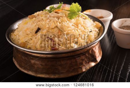 delicious biryani in a round brass bowl