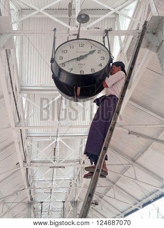 YANGON MYANMAR - APRIL 17 2013 :Burmese Man setting time on a big clock in (Rangoon) Yangon (Burma) Myanma