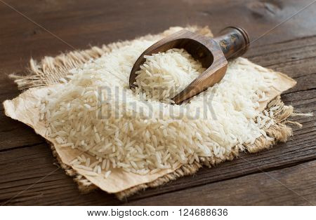 Pile of raw Basmati rice with a spoon close up