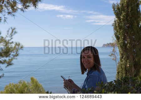 Black haired woman with phone in hands looking over shoulder with toothy smile. Waterscape on background