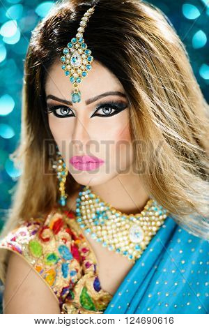 Portrait of a beautiful female model in traditional ethinic indian costume with jewellery and heavy makeup in a bridal style