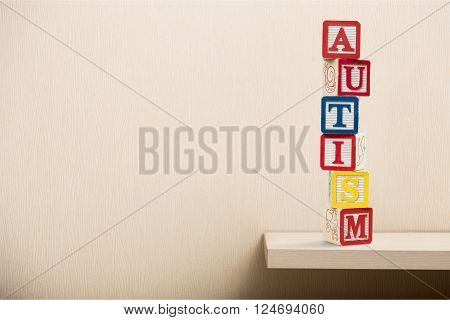 Toy blocks with word autism over light background