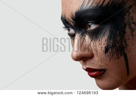 Beauty female Model with black Paint on Face looking at the Side. Creative Makeup Art Portrait for Advertising