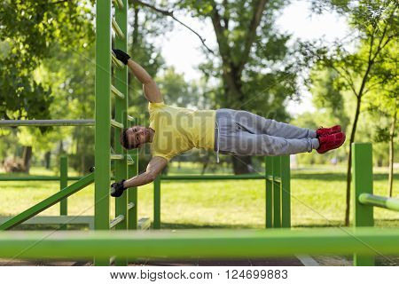 Young athlete working out in an outdoor gym doing street workout exercises