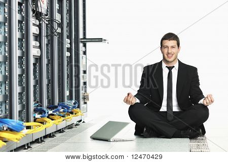 young handsome business man in black suit practice yoga and relax at network server room while representing stress control concept poster