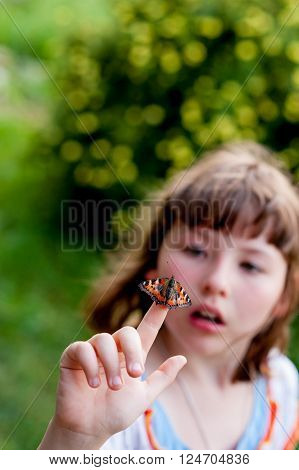 Little girl looks at a butterfly on his finger. Aglais urticae L.
