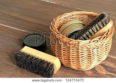 Subjects for care of footwear in a wicker basket on a brown wooden background